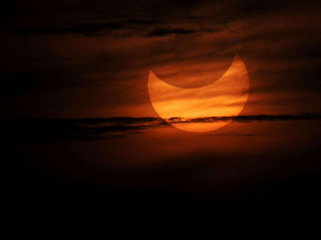 Partial solar eclipse as seen during sunrise in the coastal town of