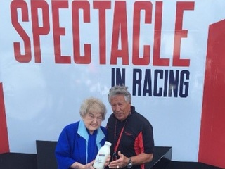 Eva Kor presented milk bottle by Mario Andretti